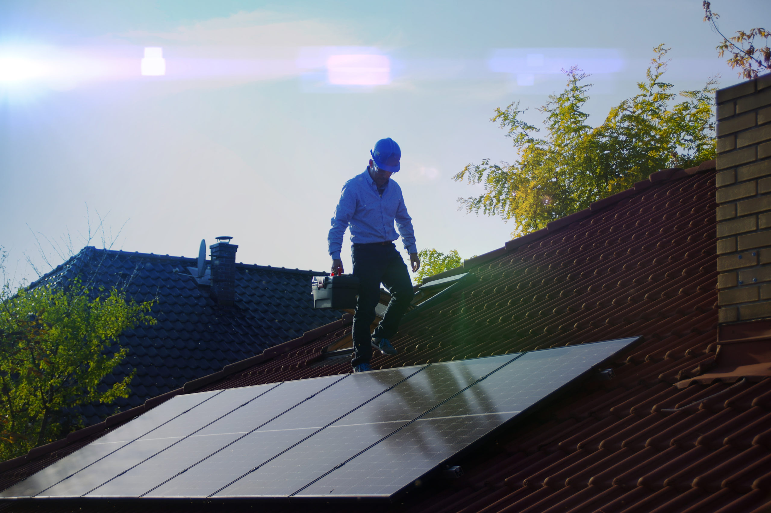 Man walk on house roof and installs solar panels. Photovoltaic, alternative and renewable energy, green power, ecology and home electricity production.