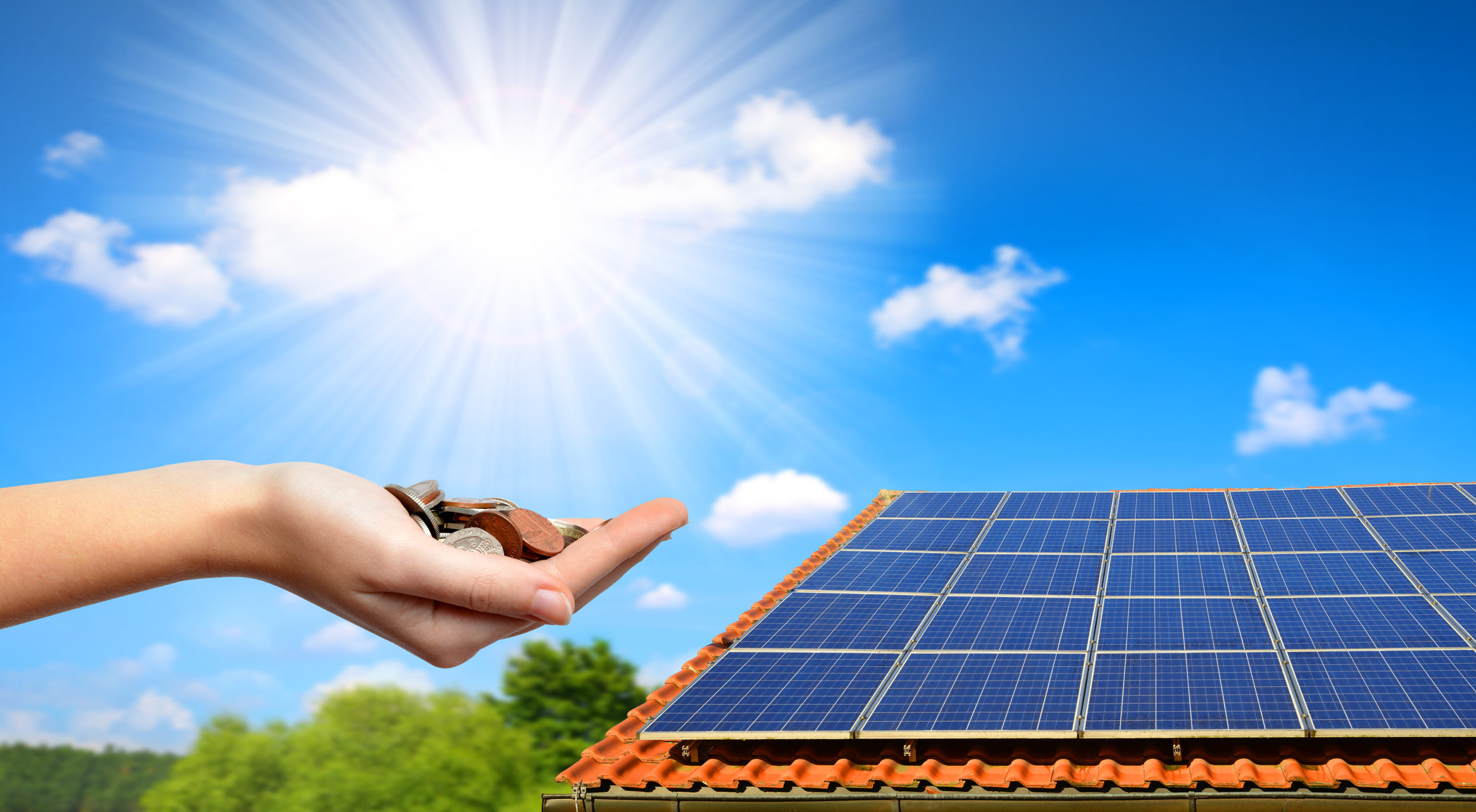 Solar panel on the roof of the house and coins in hand. The concept of money saving and clean energy.