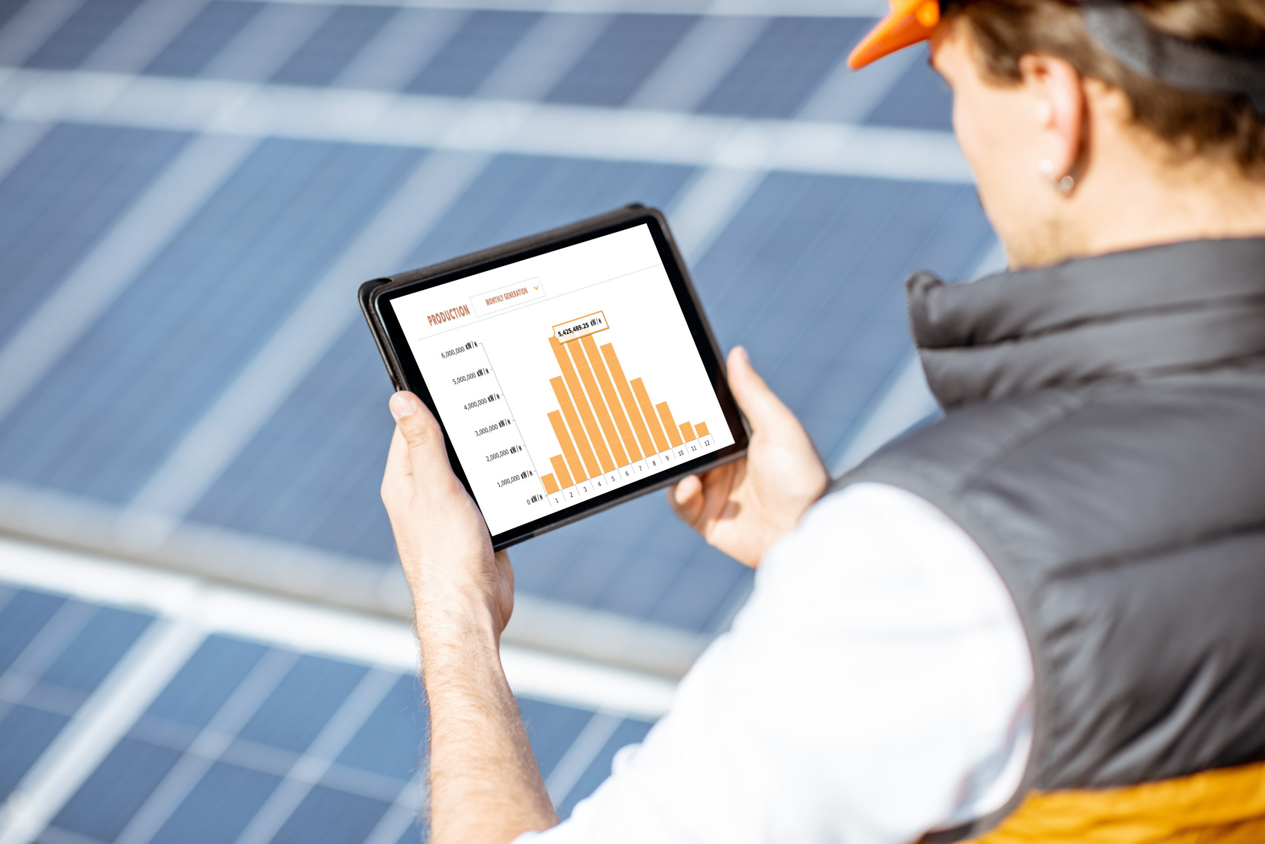 Man examining genaration of solar power plant, holding digital tablet with a chart of electricity production. Concept of online monitoring of the electric station